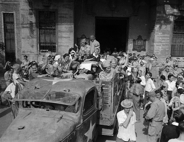 "The first truckload of American Army Nurses, the well-known ""Angels of Bataan,"" leave Santo Tomas here, where they were imprisoned after their capture by the Japanese on Correcidor Island three years ago.  This is the start of the long trip back to the United States and home. February 22, 1945 Manila, Philippines"