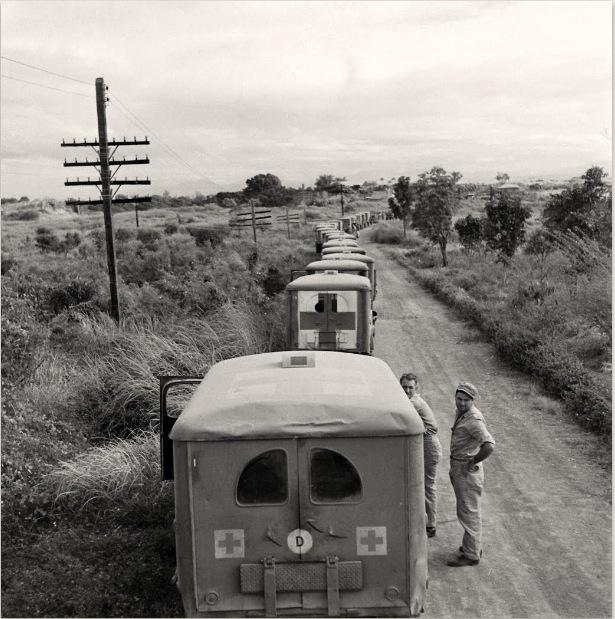 Long line of ambulances wait for the internees arrival. [Life ©Mydans]