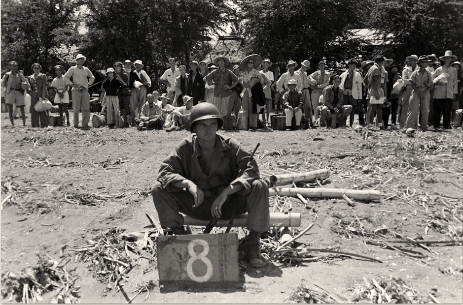 Soldier waits by assigned truck number [Life ©Mydans]