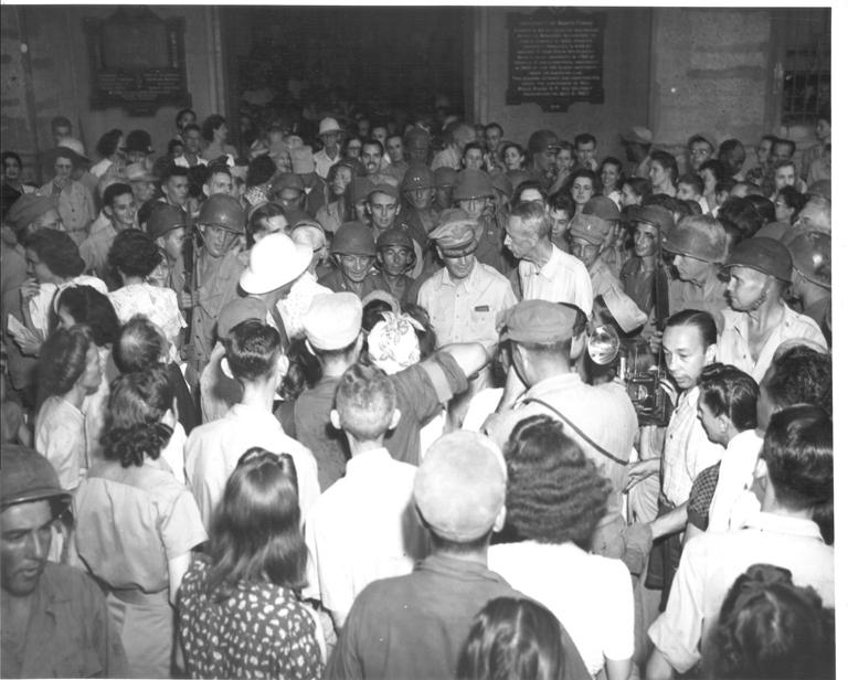 Internees crowd around Gen. MacArthur - the man of the hour.