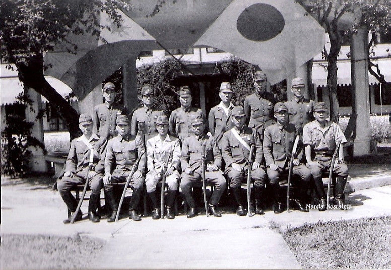 Japanese soldiers pose with flags.
